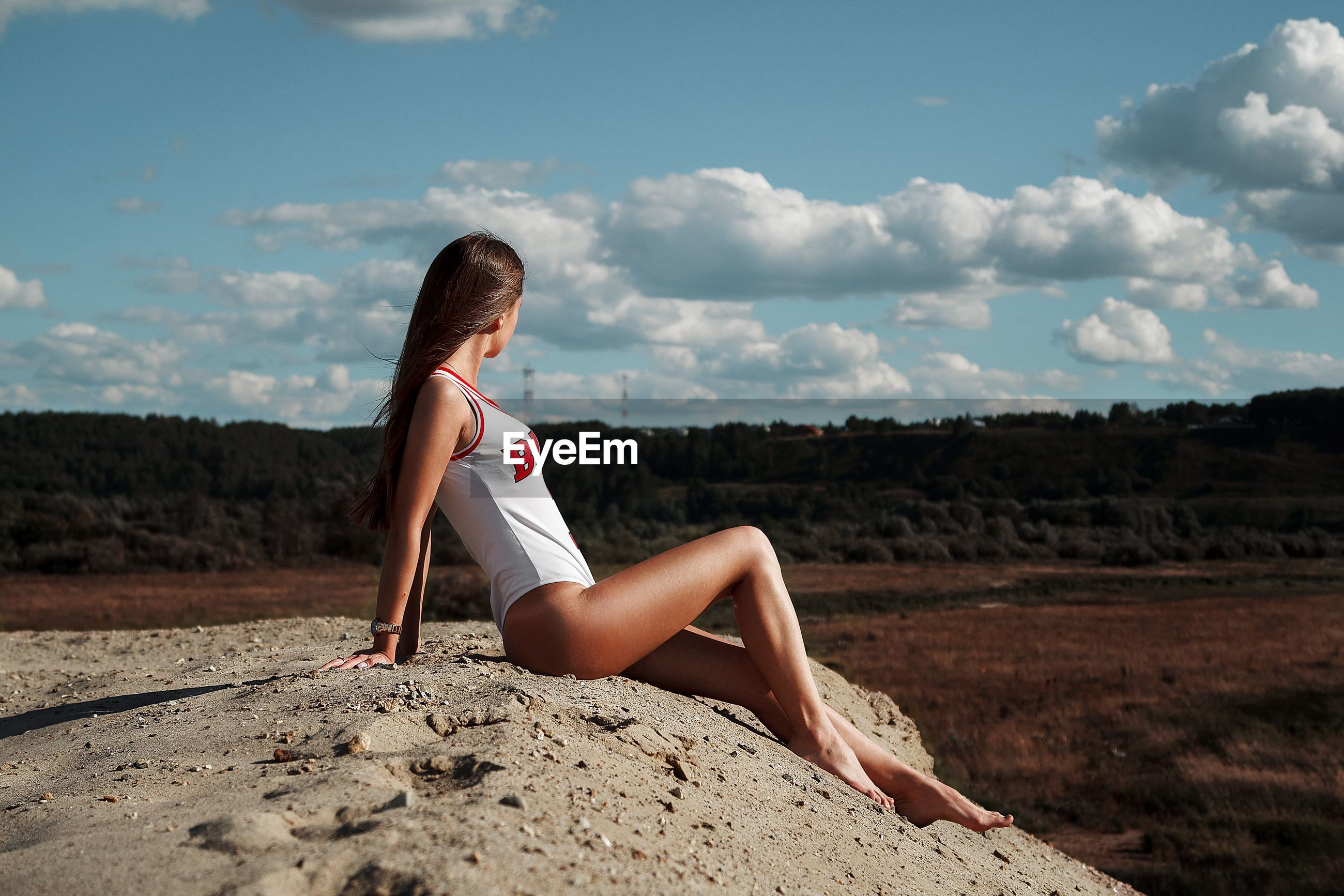 Side view of woman sitting on sand dune against sky