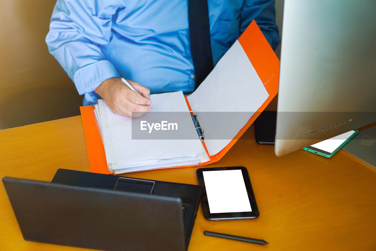 REAR VIEW OF MAN WORKING ON TABLE IN OFFICE