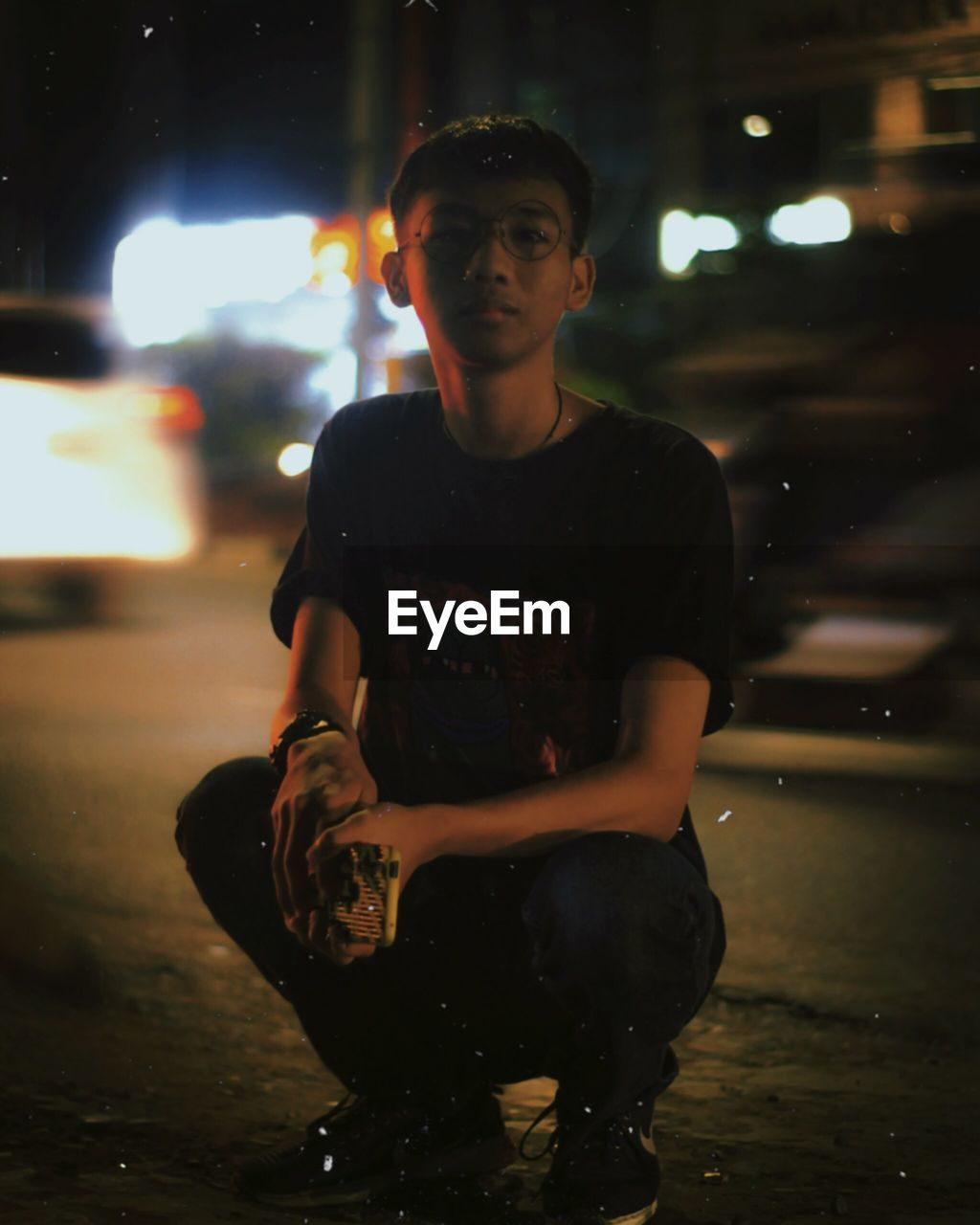Portrait of young man crouching on road at night