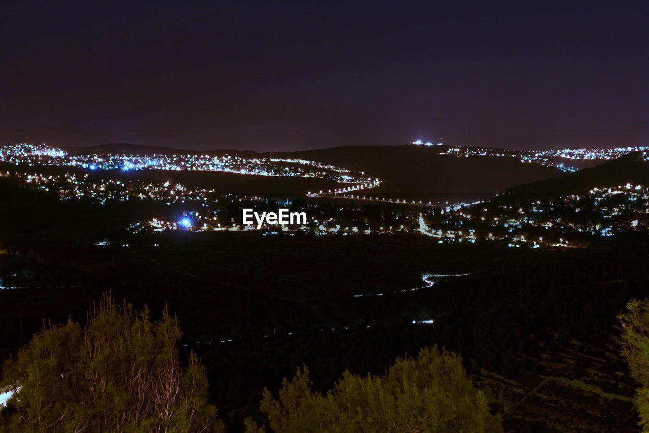 Illuminated Landscape Against Sky At Night