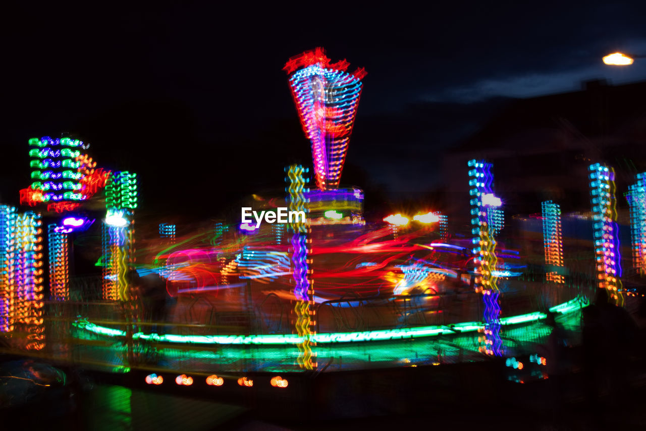 illuminated, night, amusement park, multi colored, arts culture and entertainment, blurred motion, amusement park ride, motion, speed, ferris wheel, long exposure, no people, outdoors, light trail, sky, ride, low angle view, building exterior, architecture, built structure, big wheel, carousel, city, neon