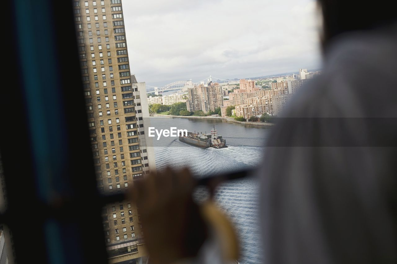 focus on background, city, architecture, built structure, building exterior, selective focus, mode of transport, water, window, river, nautical vessel, cityscape, day, indoors, transportation, ferry, looking through window, real people, one person, skyscraper, sky, close-up