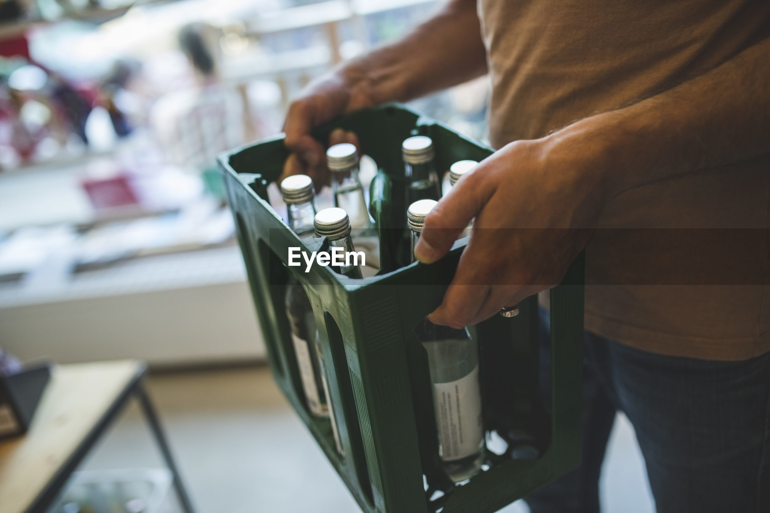 Midsection of salesman carrying bottles in crate at deli