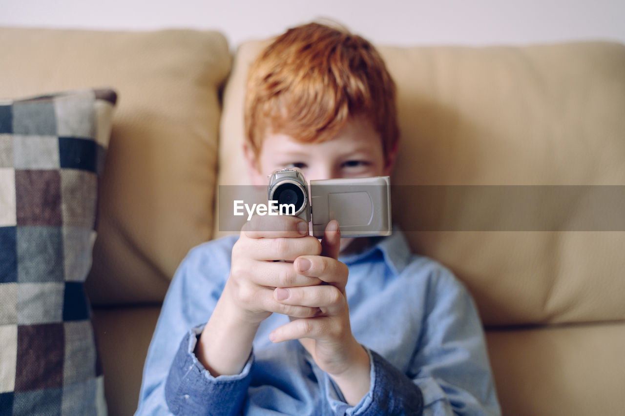 Portrait of boy holding camera while sitting on sofa