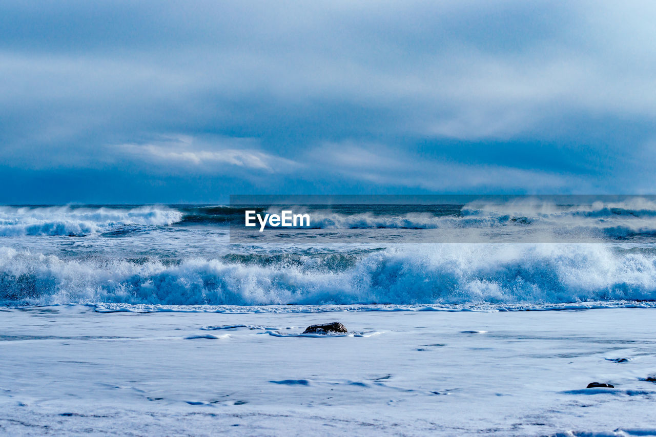 BREAKING WAVES IN ICELAND UNDER CLOUDY SKY