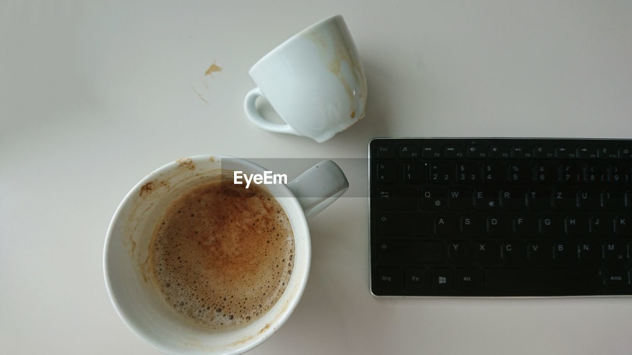 drink, cup, coffee, coffee cup, food and drink, refreshment, coffee - drink, mug, indoors, still life, table, technology, wireless technology, keyboard, no people, high angle view, laptop, computer, computer keyboard, freshness, crockery, hot drink, tea cup