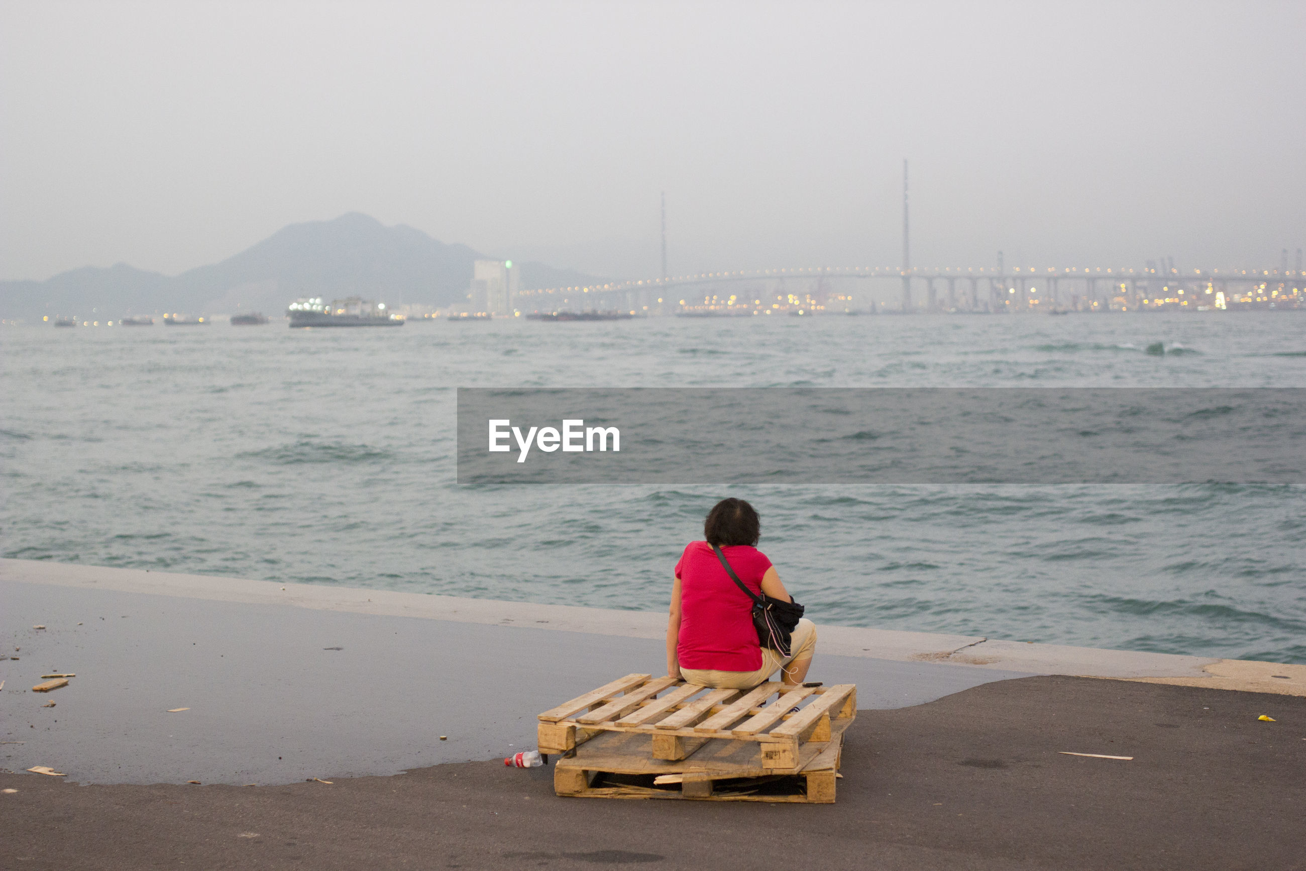 Rear view of woman sitting on wooden pallet at beach