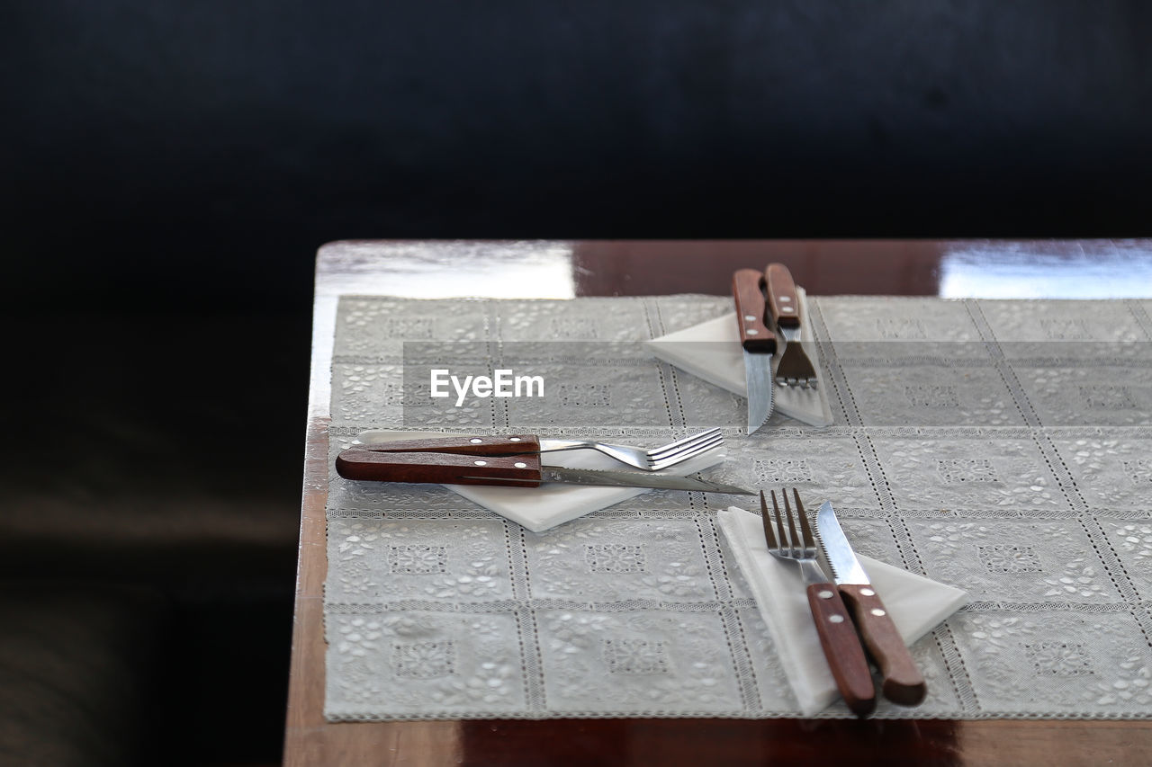 High angle view of cutlery and napkins on dining table