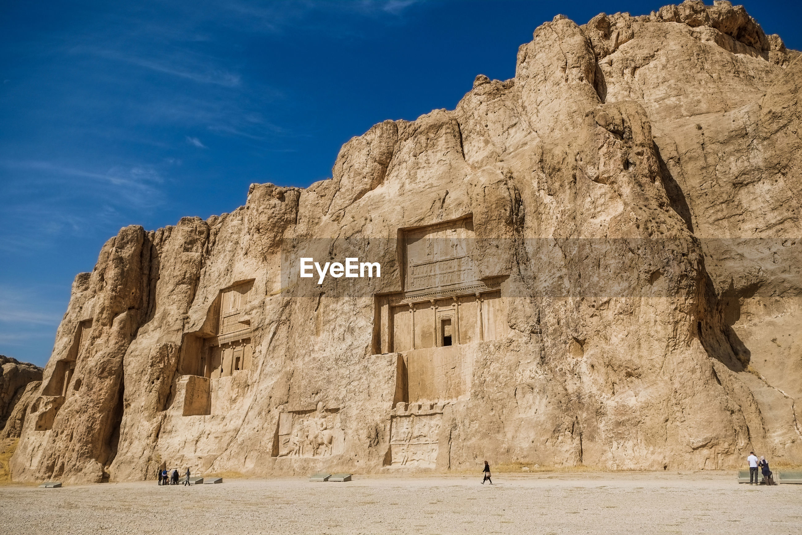 Landscape of the naqsh-e rustam shows large tombs cut high into the cliff face. fars province, iran.