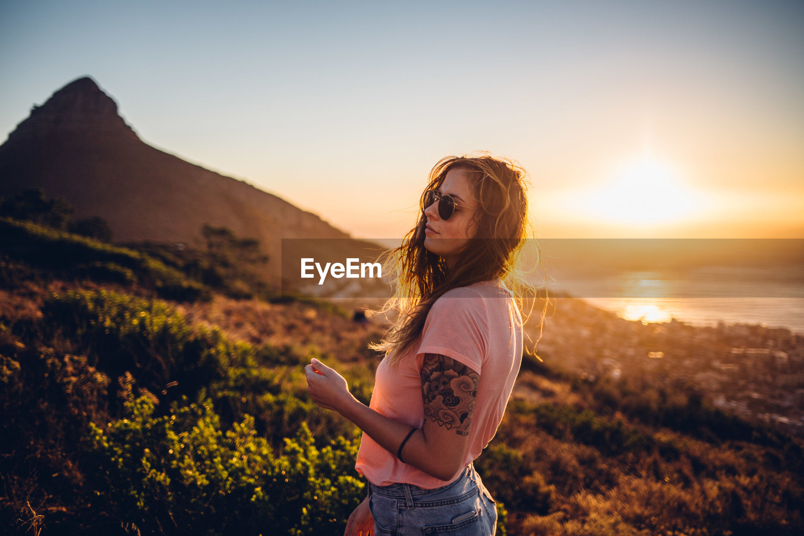 YOUNG WOMAN WEARING SUNGLASSES STANDING ON LAND AT SUNSET