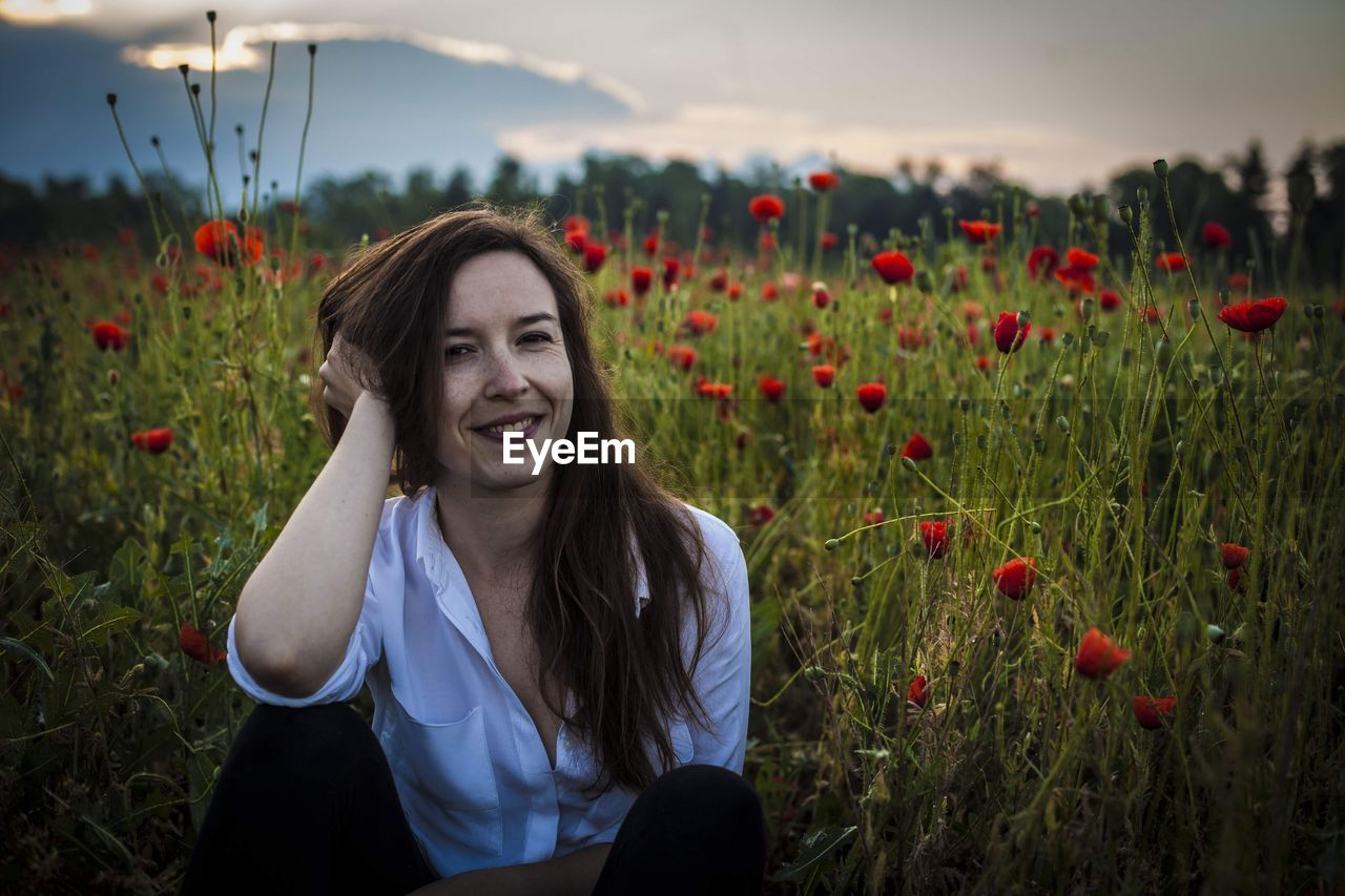 Portrait Of Smiling Young Woman Sitting By Poppy Flowers On Field