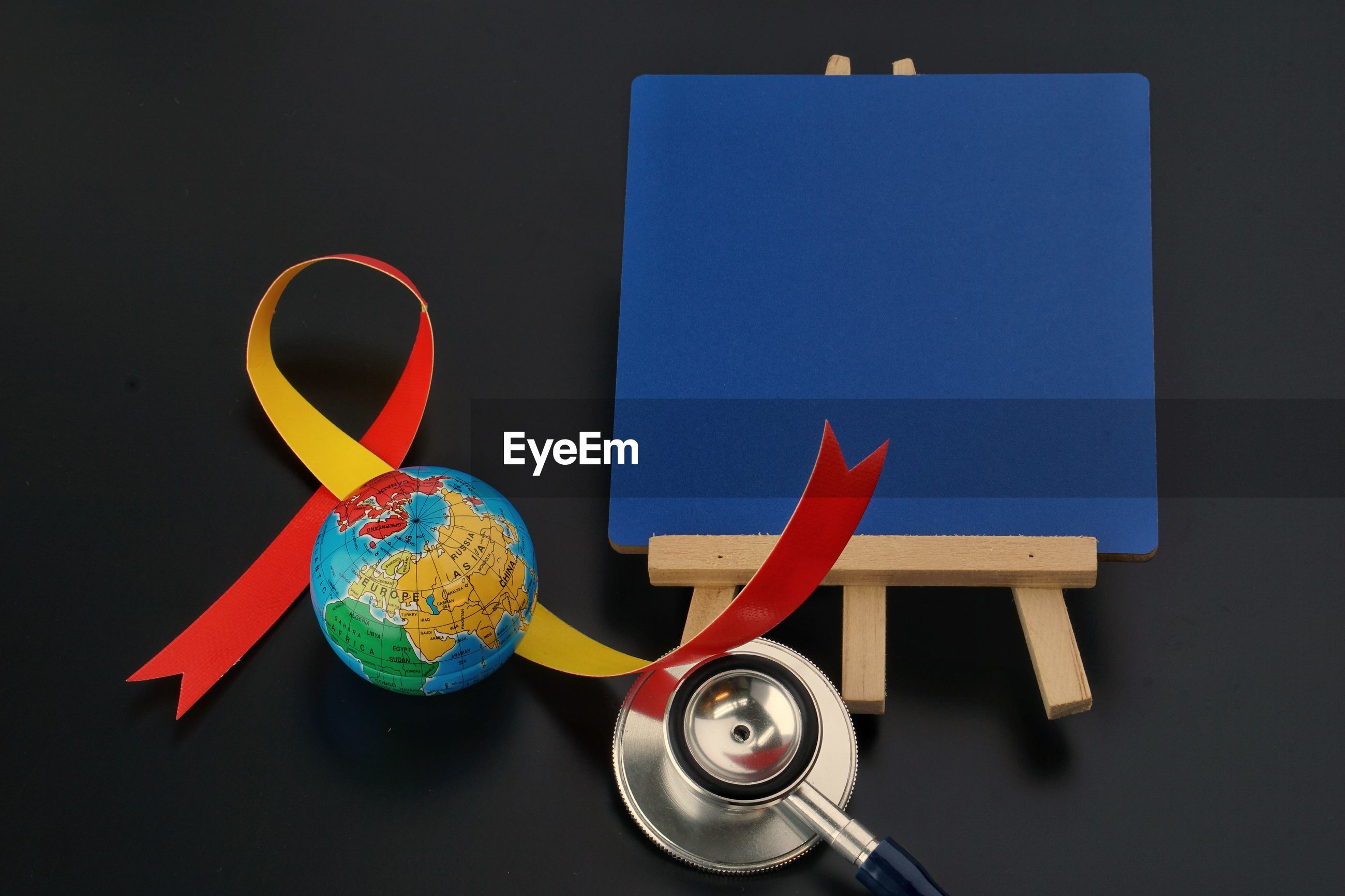 Stethoscope with globe and placard on black background
