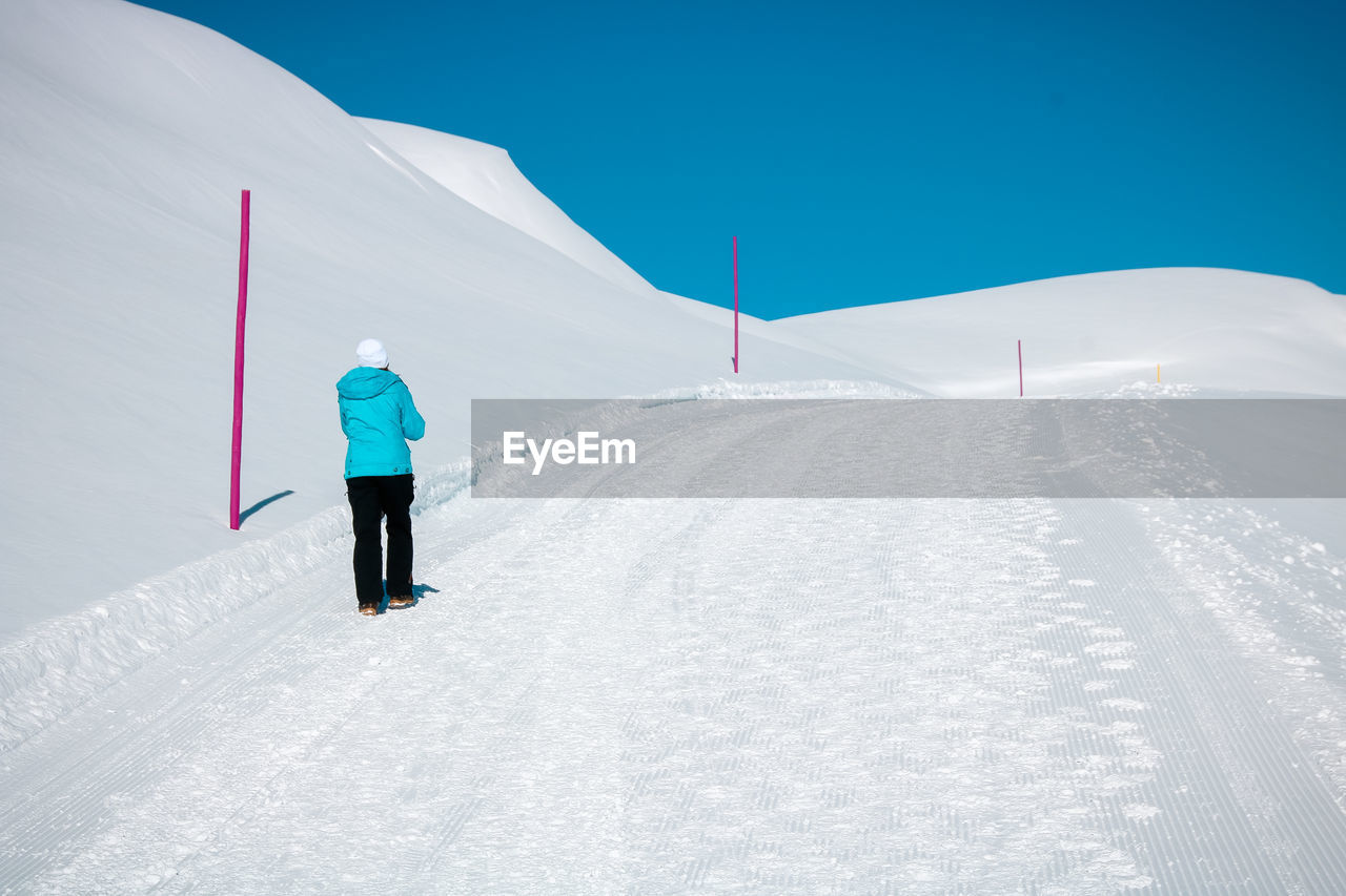 winter, cold temperature, snow, mountain, real people, rear view, one person, white color, lifestyles, leisure activity, beauty in nature, winter sport, sky, skiing, sport, scenics - nature, unrecognizable person, full length, warm clothing, mountain range, snowcapped mountain