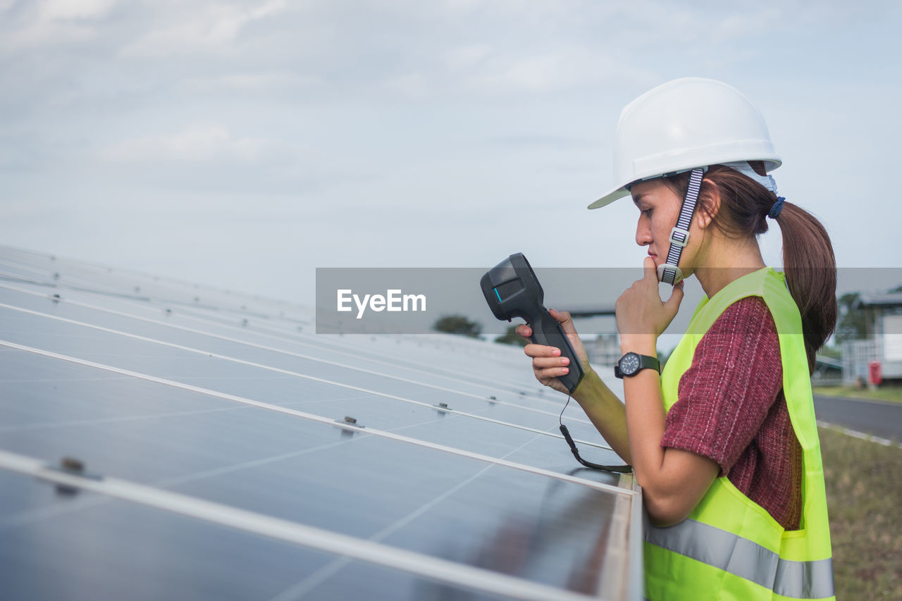 technology, one person, sky, real people, holding, alternative energy, renewable energy, environmental conservation, solar panel, lifestyles, mobile phone, solar energy, young women, side view, adult, young adult, occupation, fuel and power generation, telephone, wireless technology, outdoors, sustainable resources