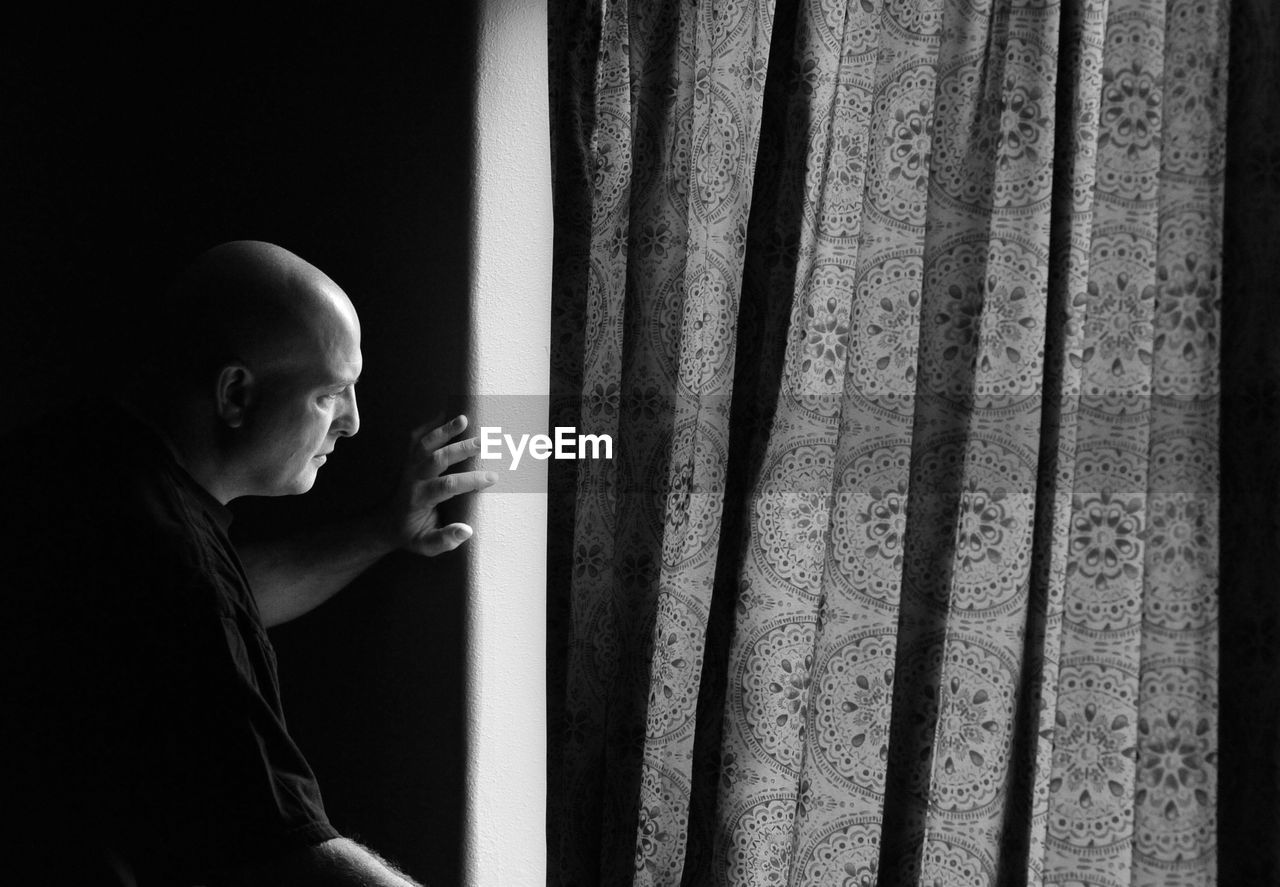 Side View Of Mature Man Looking Through Window At Home