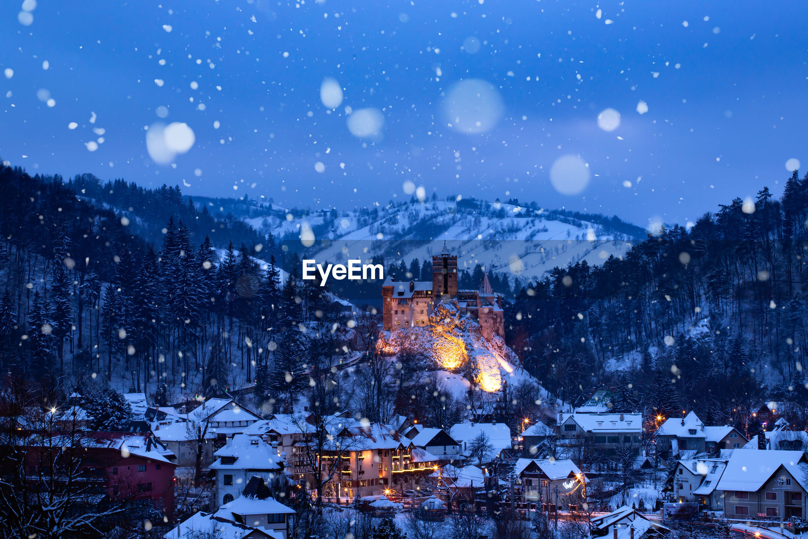 Illuminated buildings in city at night during winter