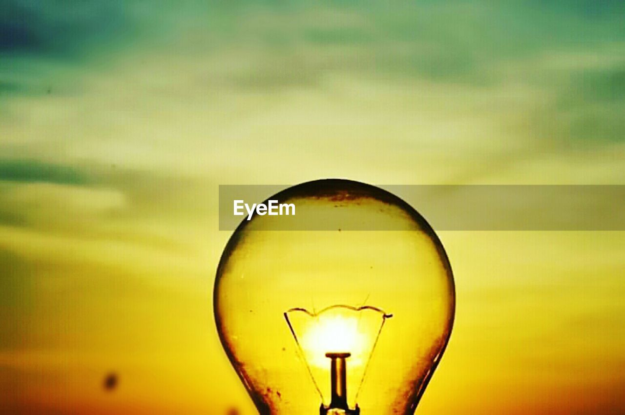 lighting equipment, light bulb, illuminated, electricity, sunset, glowing, bulb, sky, close-up, filament, no people, low angle view, yellow, outdoors, technology, nature, day