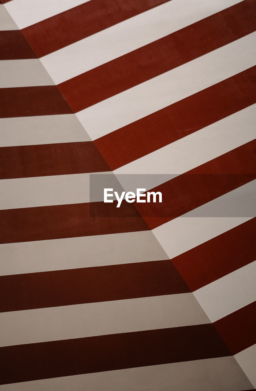 full frame, backgrounds, pattern, red, no people, striped, wall - building feature, indoors, architecture, close-up, built structure, white color, flag, repetition, low angle view, day, design, textured, shape