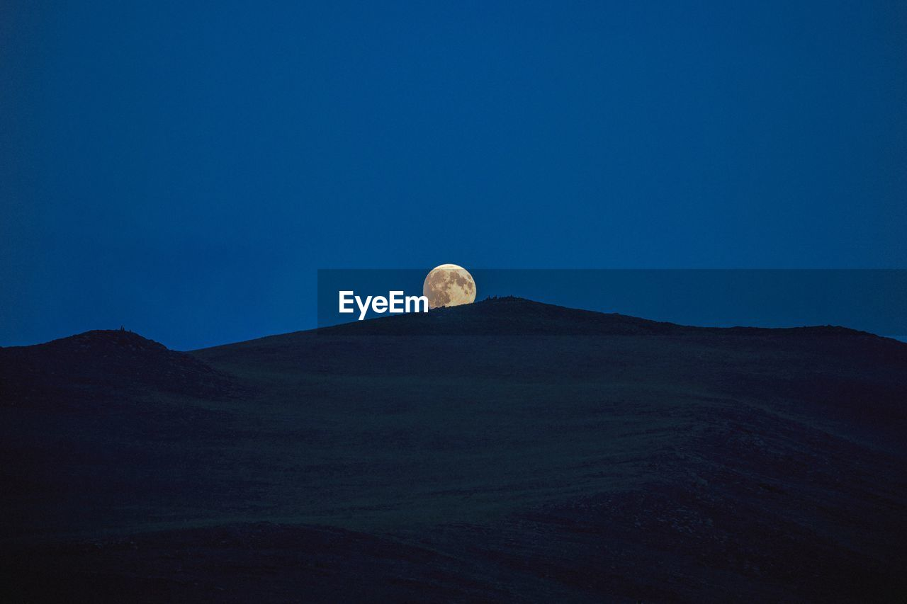 sky, moon, scenics - nature, copy space, beauty in nature, blue, mountain, no people, tranquil scene, clear sky, nature, tranquility, non-urban scene, landscape, environment, idyllic, full moon, land, low angle view, astronomy, outdoors, mountain peak, planetary moon, arid climate
