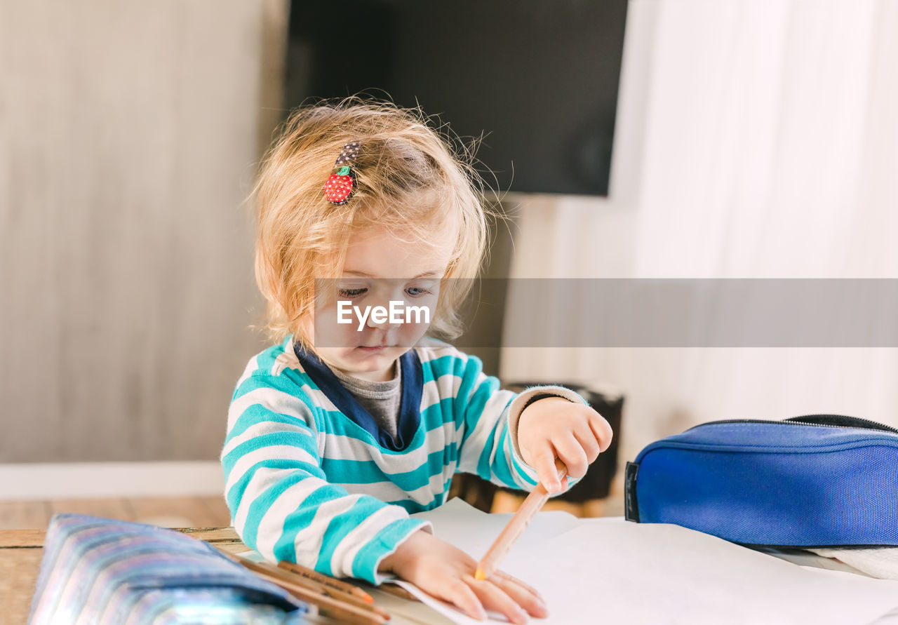 Girl Holding Pencil At Home