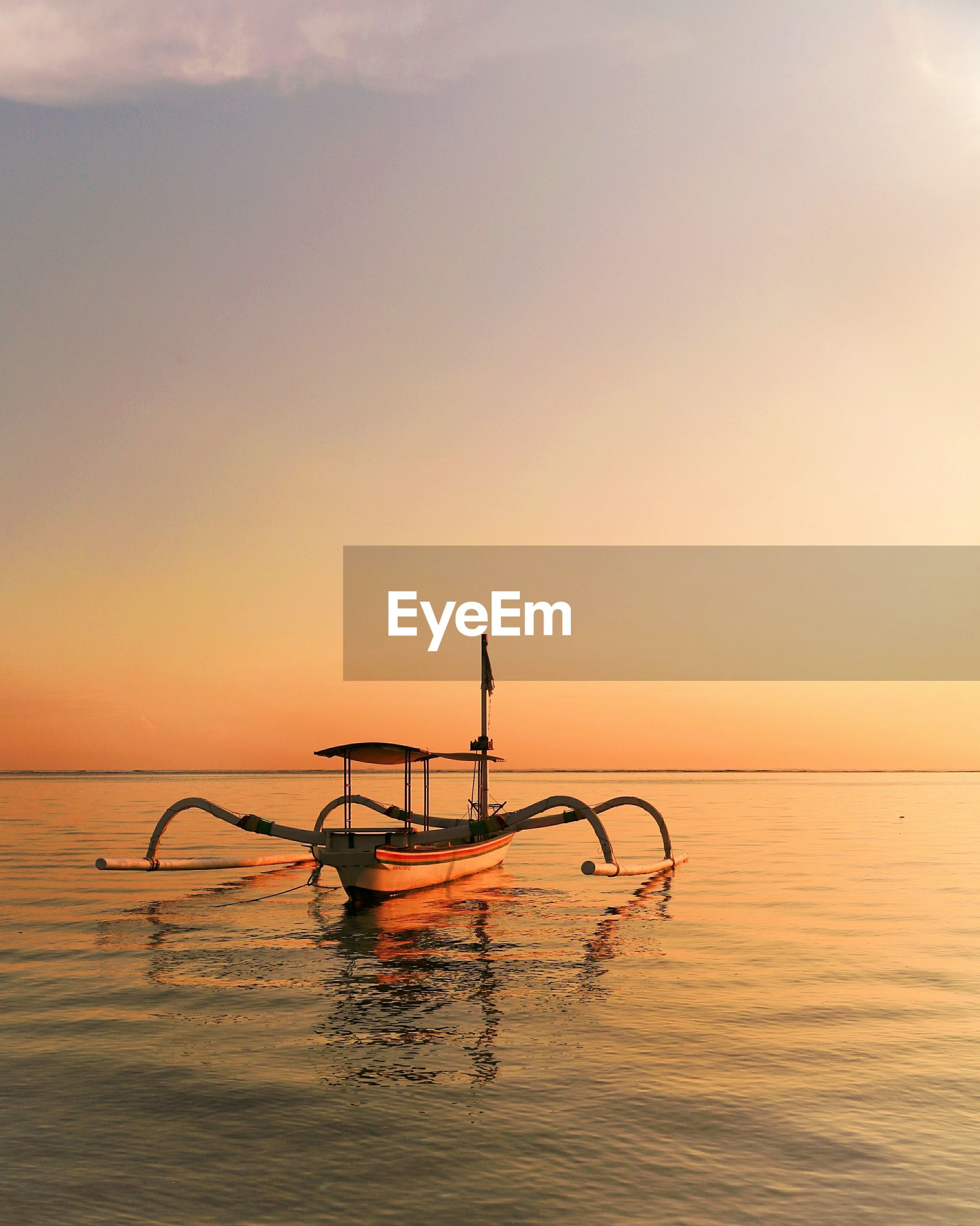 SILHOUETTE BOAT AGAINST SEA DURING SUNSET