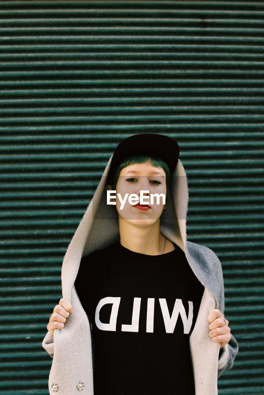 Portrait Of Punk Woman Standing Against Green Shutter