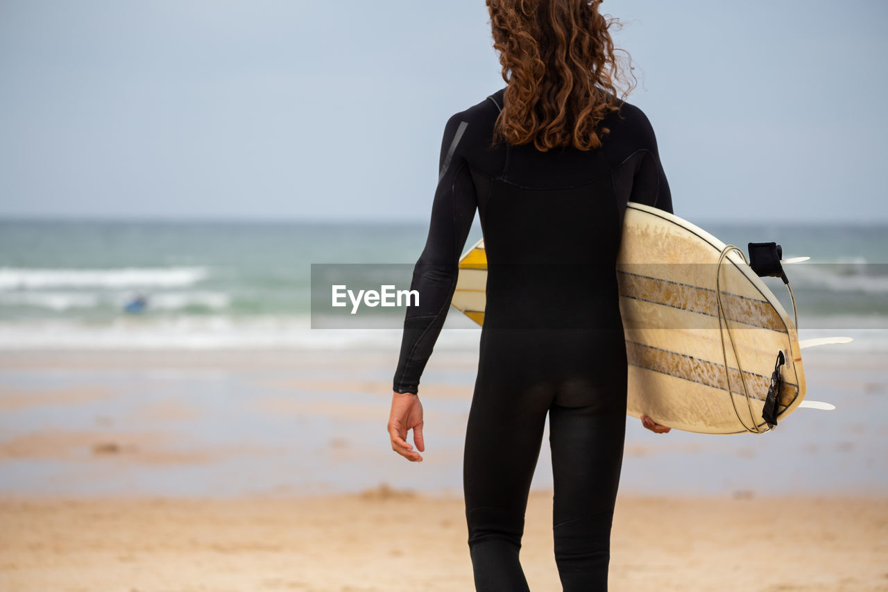 Rear view of woman holding surfboard while walking at beach against sky
