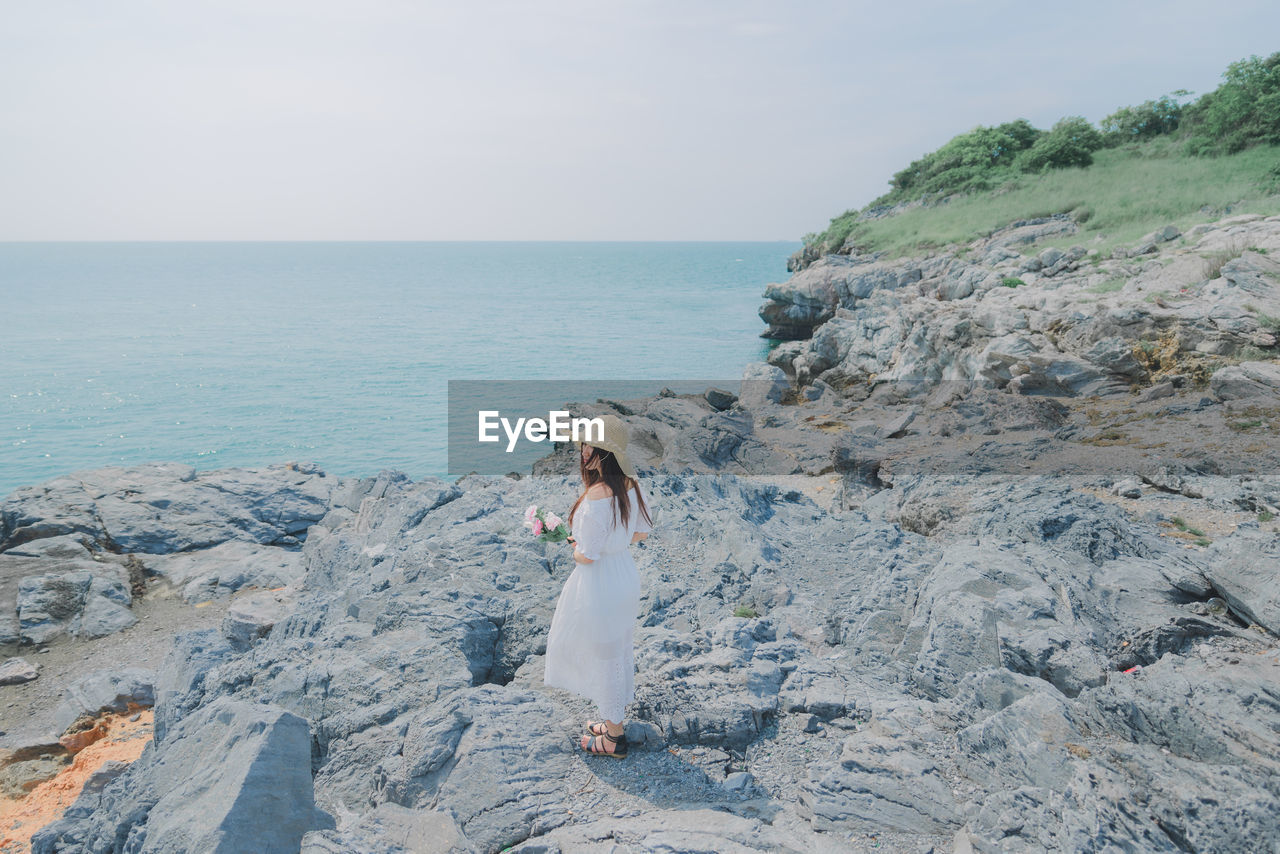 Full length of woman standing on rock by sea against sky