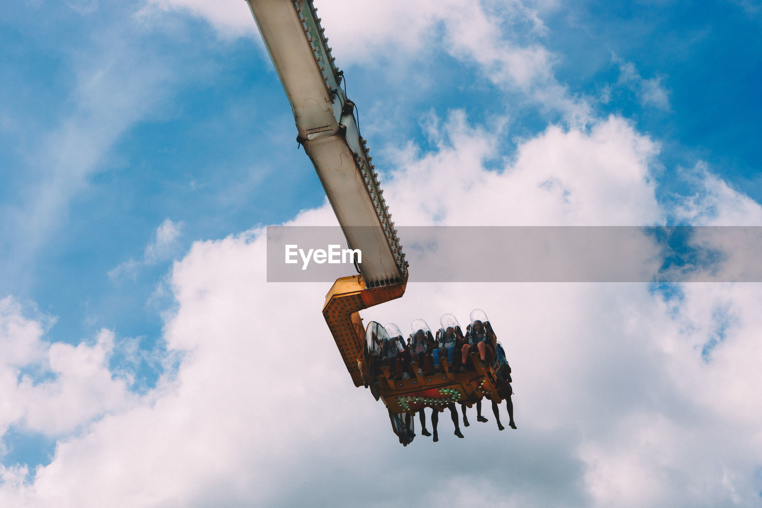 Low angle view of people enjoying suspended ride at amusement park against cloudy sky