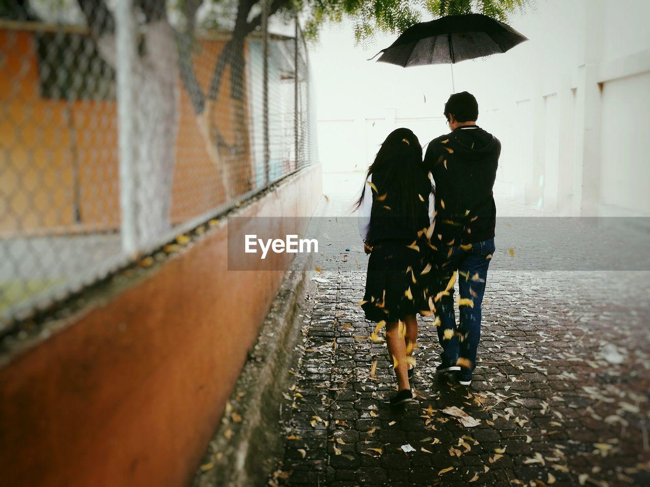 Rear View Of Couple Walking On Walkway