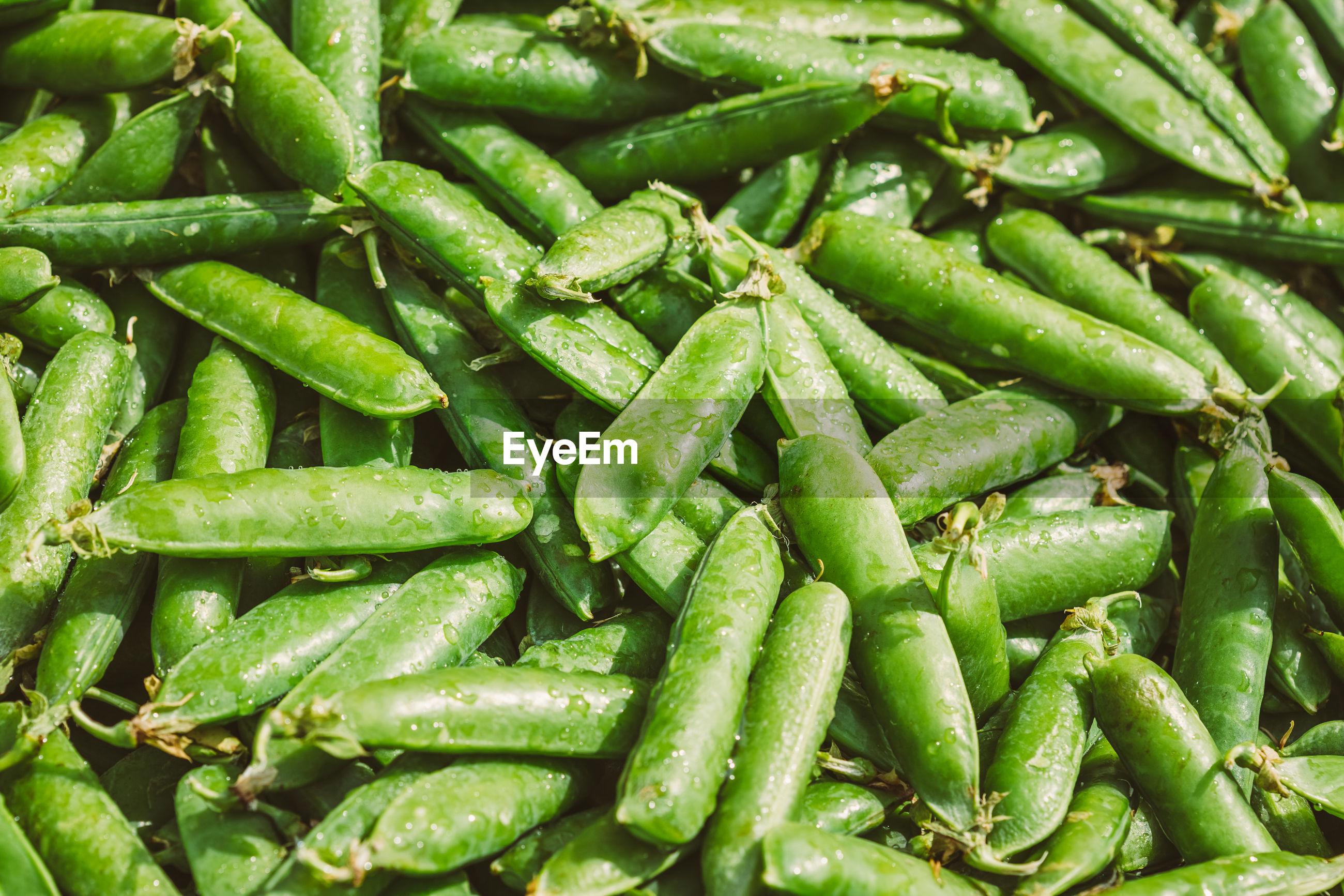 Full frame shot of wet green peas for sale at market