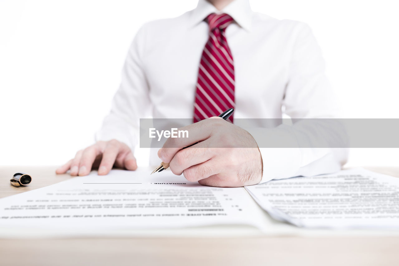 Midsection of businessman signing document at desk against white background