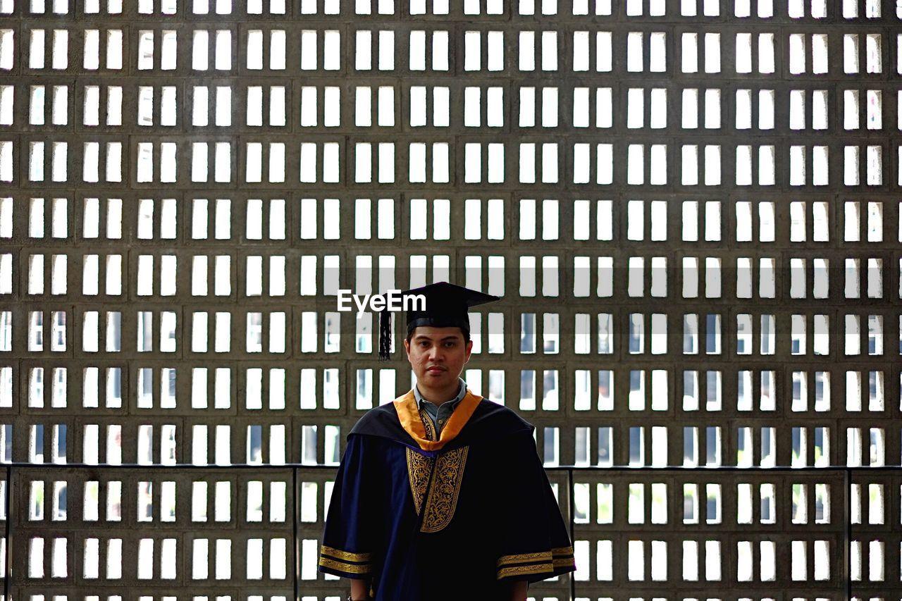 Portrait Of Man In Graduation Gown Standing Against Window