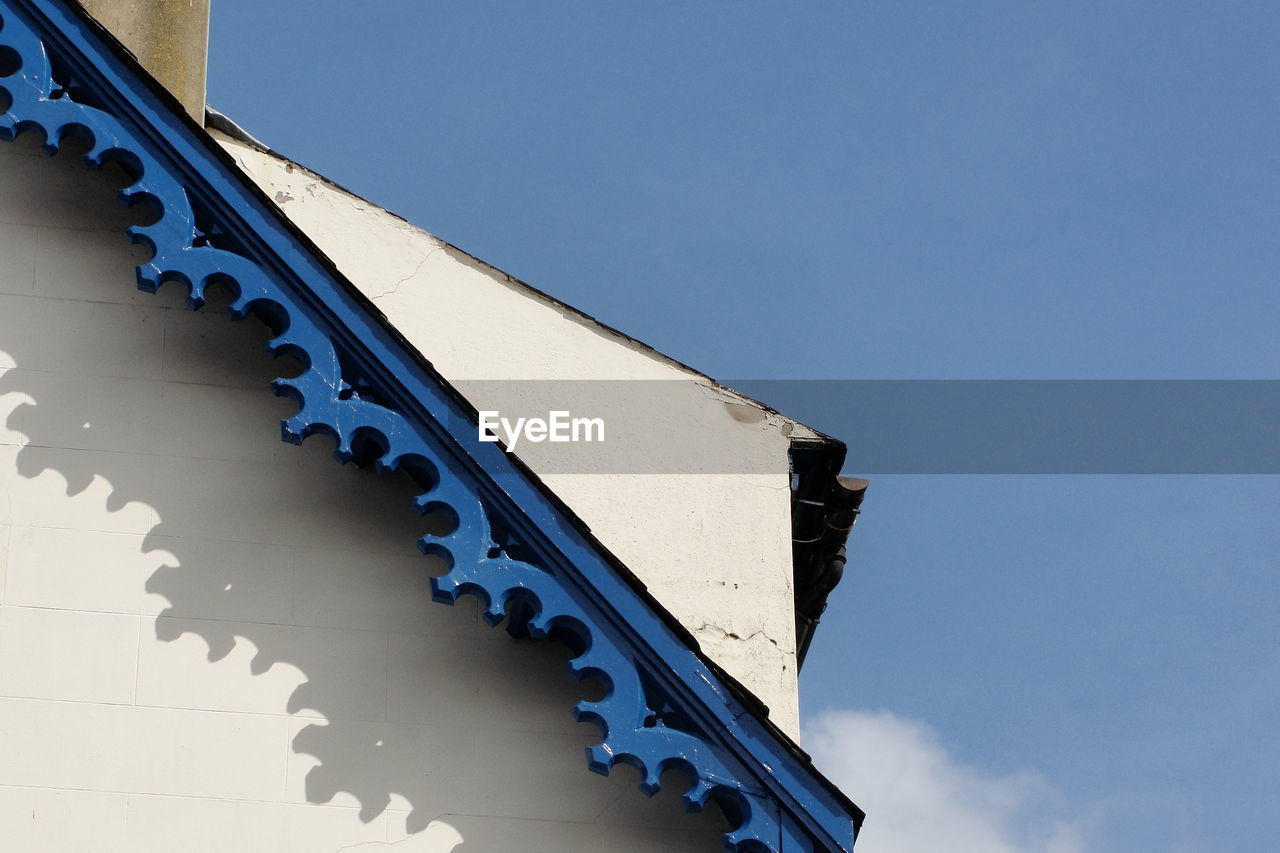 Low angle view of blue metallic design on house against sky