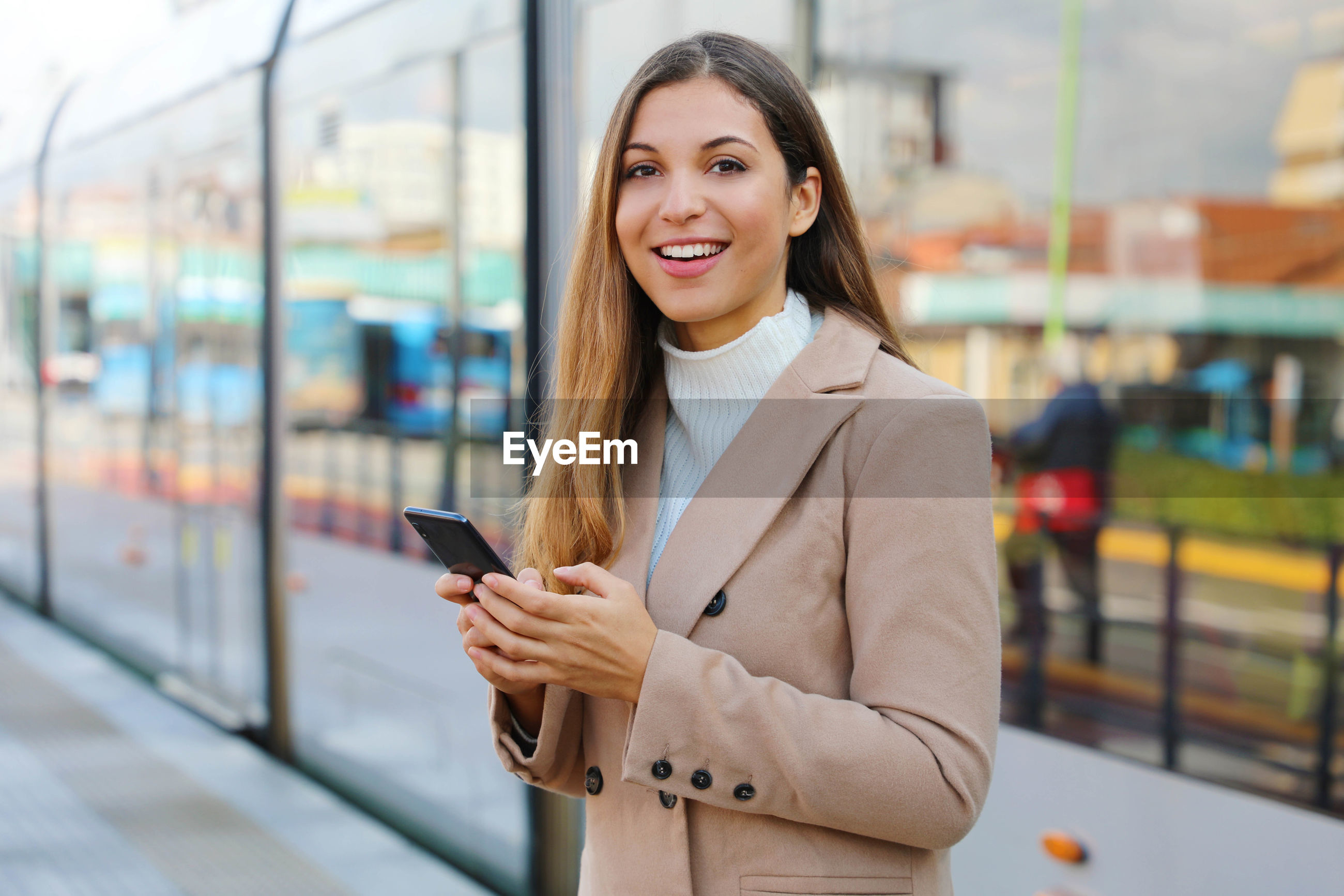 Portrait of happy young woman using phone while standing against train at railroad station