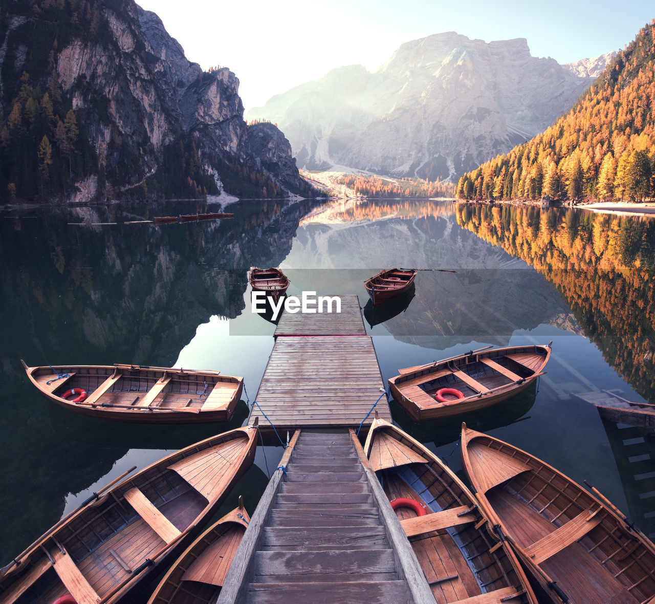 Boats moored around jetty in lake against mountains