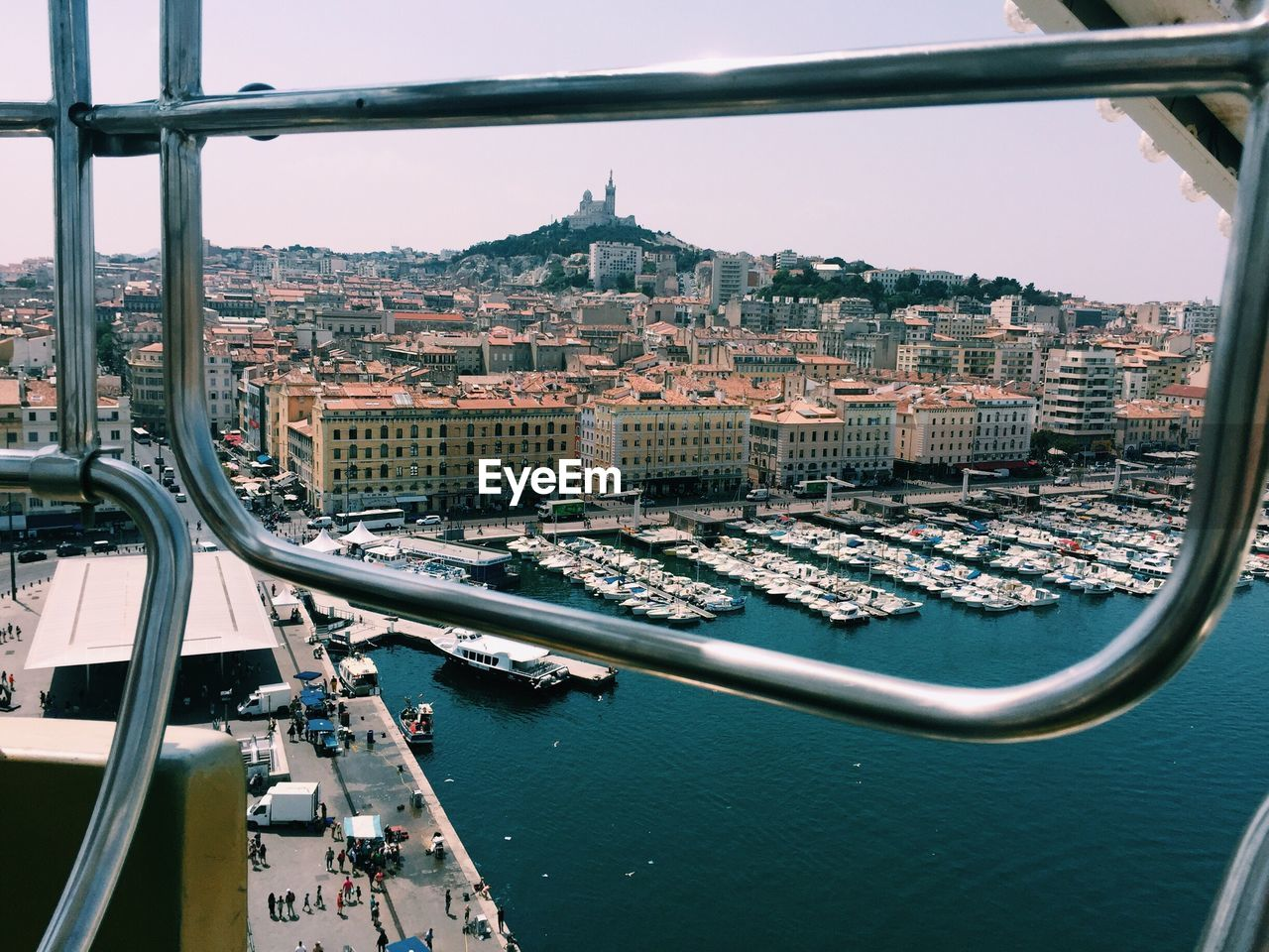 Boats Moored At Harbor In City Seen Through Railing Of Ferris Wheel
