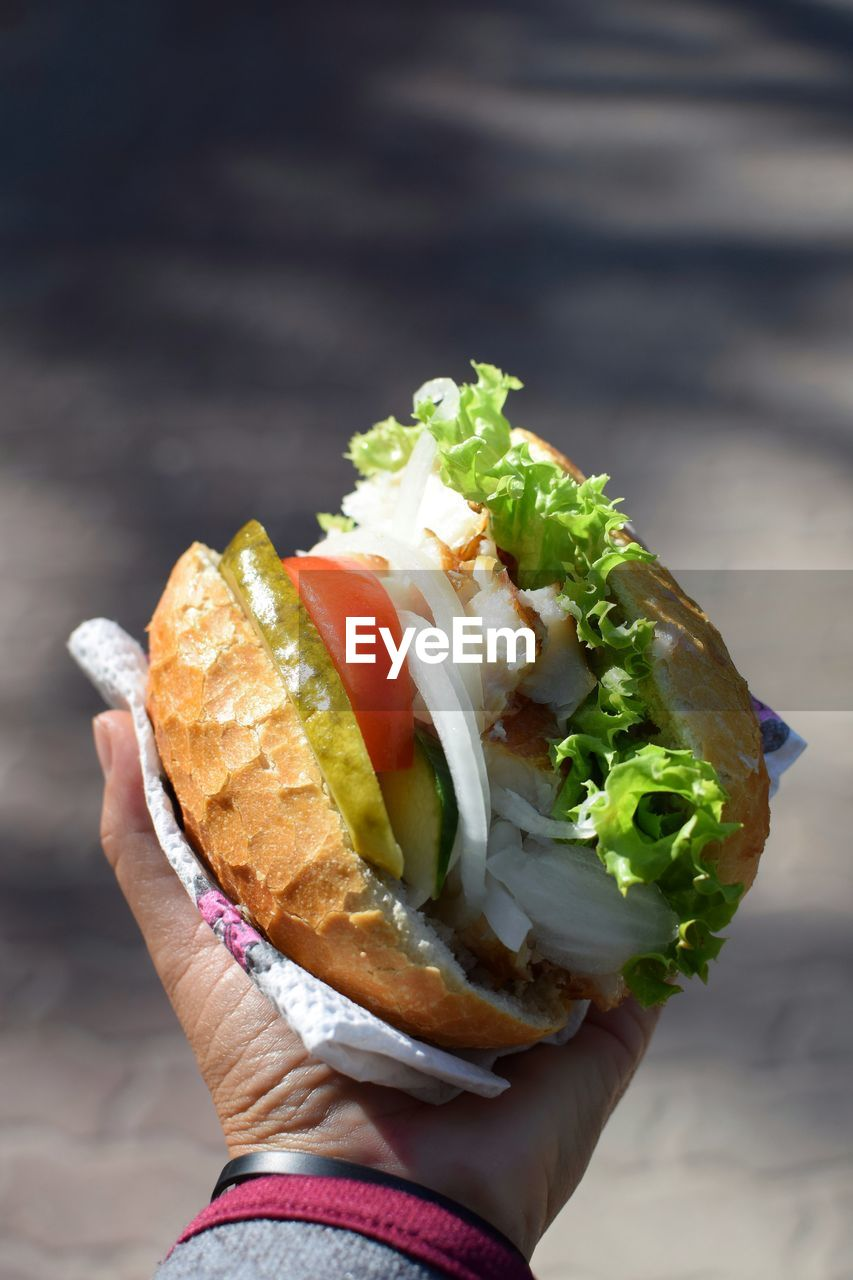 Cropped Hand Holding Burger In Sunny Day