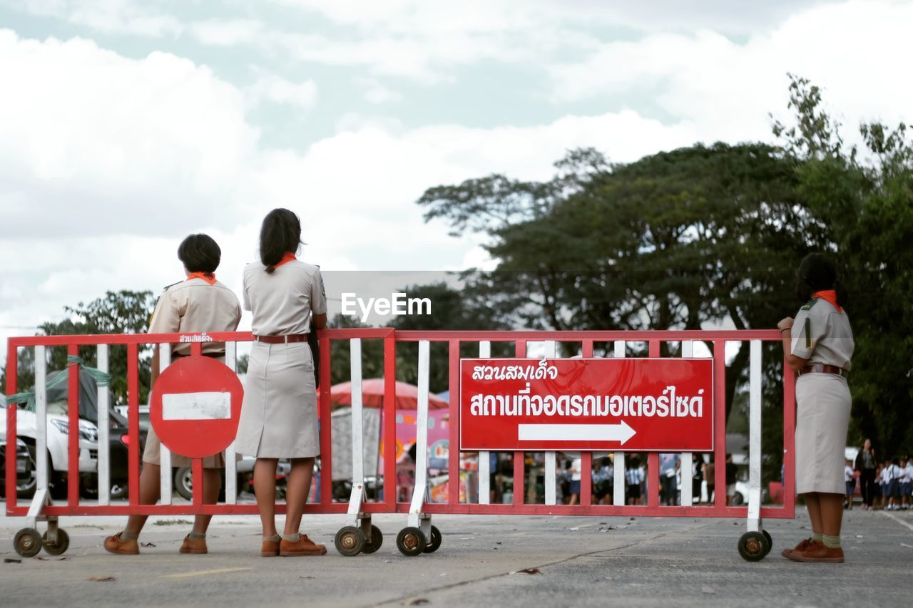 Rear View Of Women Standing By Red Sign Board Against Sky