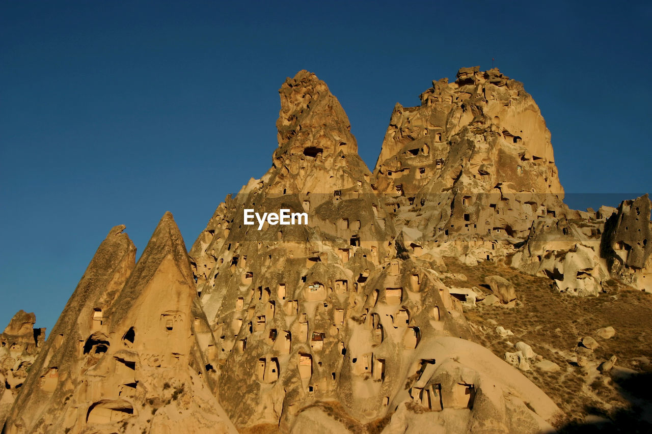sky, nature, history, the past, rock formation, clear sky, low angle view, ancient, solid, travel destinations, no people, sunlight, blue, travel, day, rock, ancient civilization, architecture, geology, scenics - nature, arid climate, climate, outdoors, eroded, archaeology