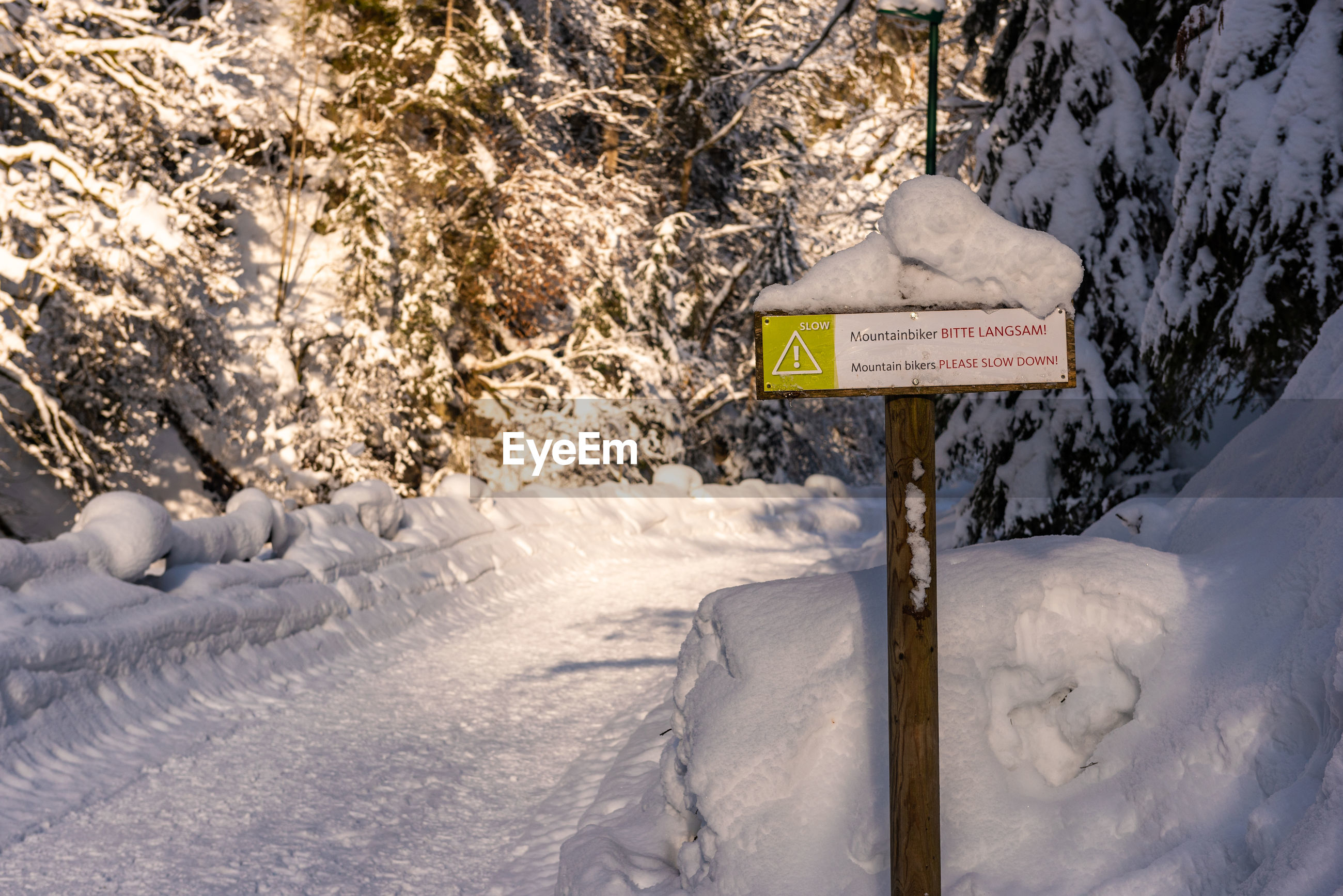 Mountain bikers, please slow down. traffic sign, warning, winter services. austria