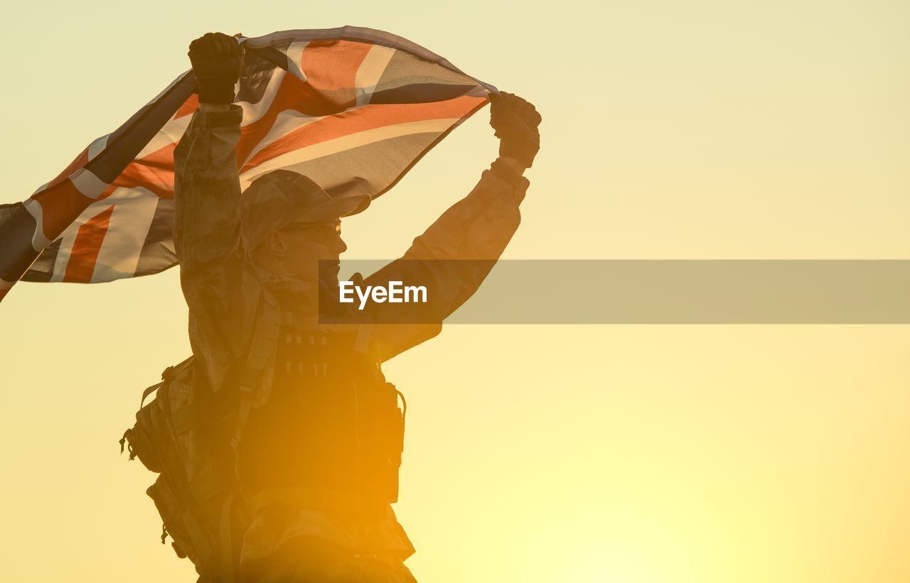 Low Angle View Of Soldier Holding British Flag Against Clear Sky During Sunset