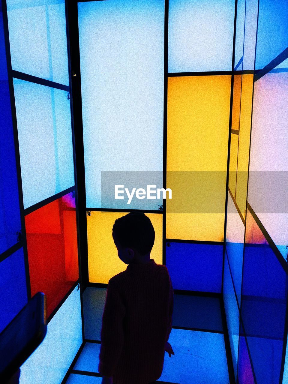Rear View Of Silhouette Boy Standing By Colorful Wall