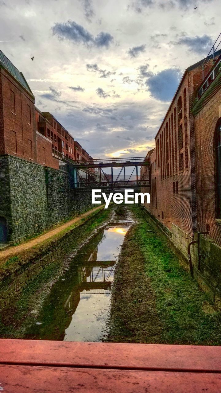 cloud - sky, architecture, built structure, sky, water, building exterior, building, nature, direction, no people, reflection, sunset, the way forward, canal, residential district, footpath, transportation, connection, grass, outdoors, long