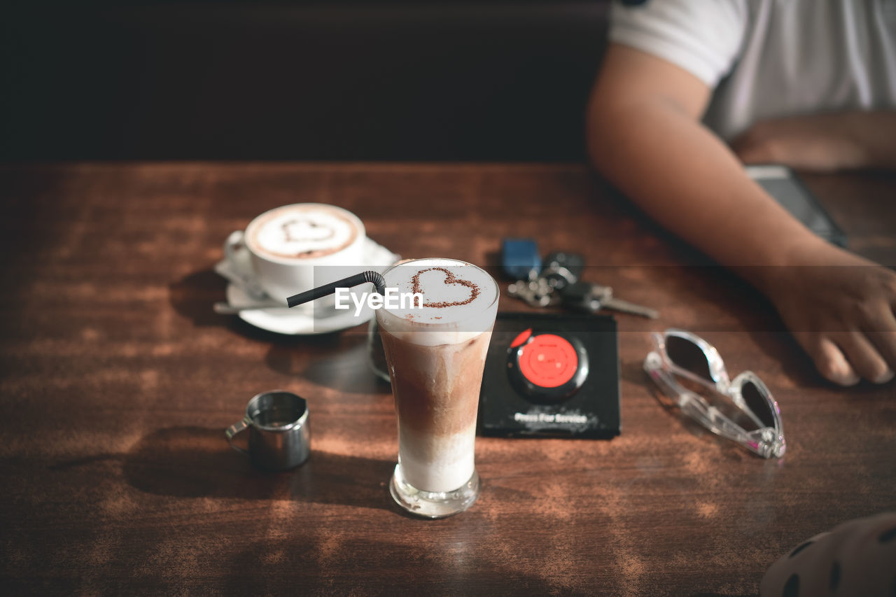 drink, table, food and drink, coffee, refreshment, indoors, coffee - drink, wood - material, frothy drink, mug, one person, human hand, hand, real people, cup, coffee cup, high angle view, freshness, food, still life, hot drink, glass, latte