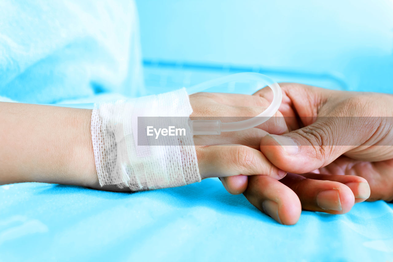 Close-Up Of Hand Holding Patient At Hospital Bed