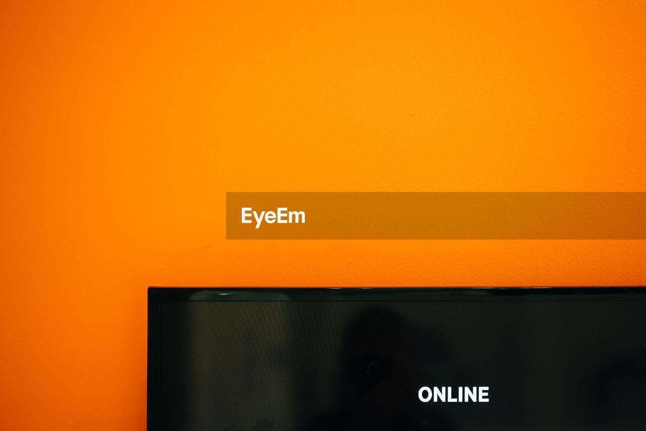 Cropped Image Of Desktop Pc Against Orange Background