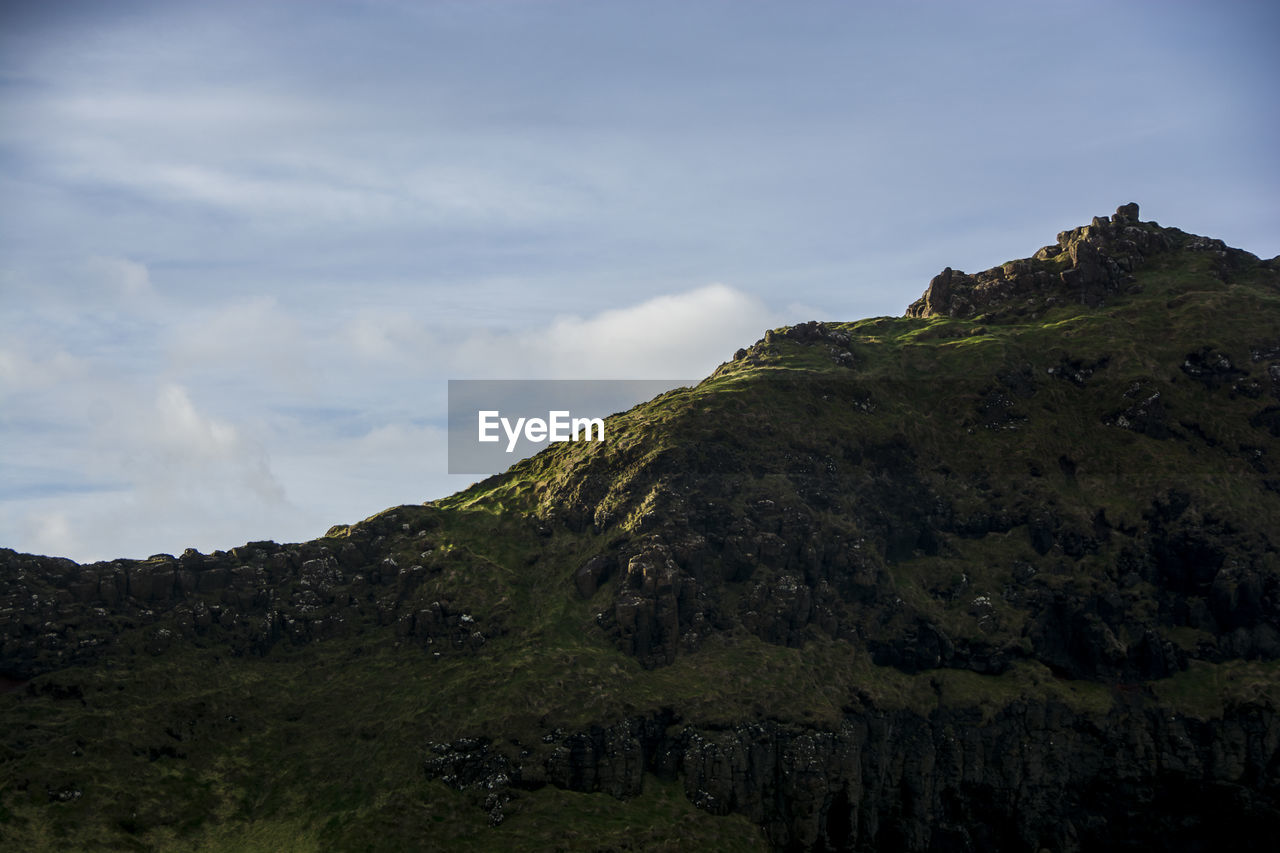 sky, mountain, cloud - sky, beauty in nature, tranquility, scenics - nature, tranquil scene, plant, nature, non-urban scene, no people, day, rock, land, tree, environment, landscape, outdoors, low angle view, green color, mountain peak, formation