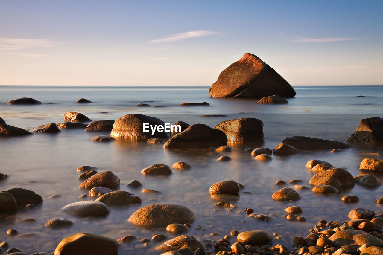 Surface level view of calm pebble beach at sunrise