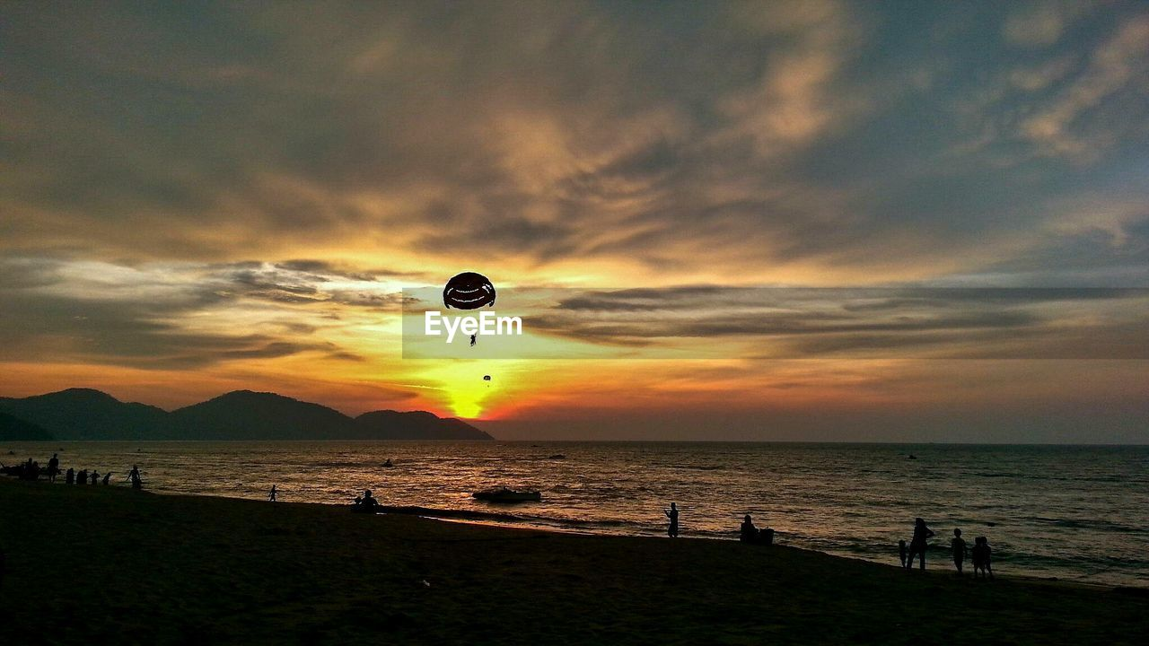 sea, sky, water, cloud - sky, scenics - nature, sunset, beach, beauty in nature, land, nature, horizon over water, silhouette, incidental people, horizon, flying, mid-air, tranquil scene, tranquility, unrecognizable person, outdoors, parasailing